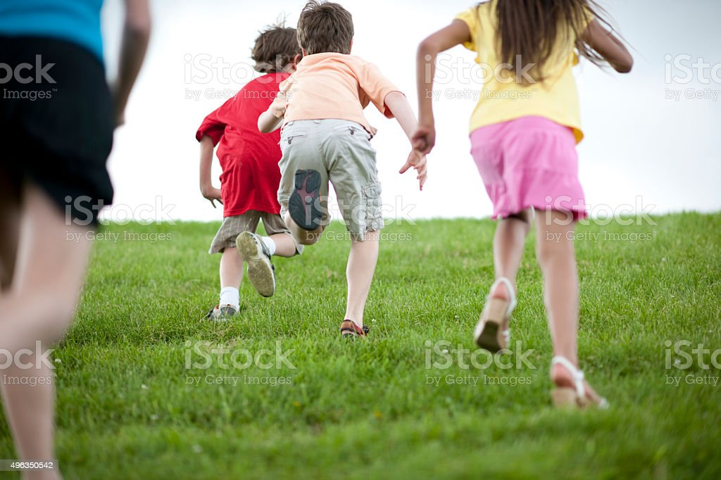 Children Playing Tag While Running Up a Hill stock photo