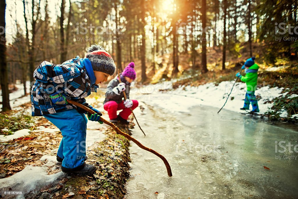 Children playing with a frozen puddle in winter stock photo