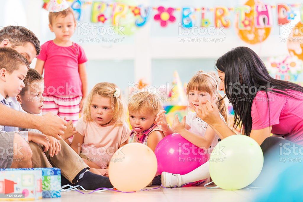 Children playing with animators at birthday party. stock photo