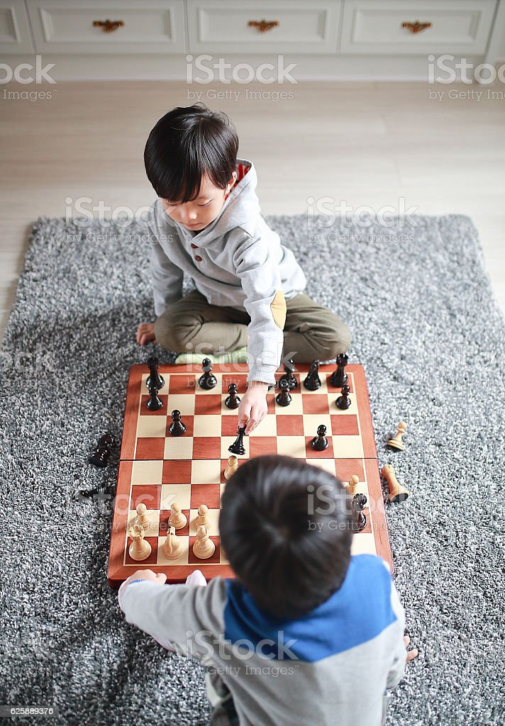 Children playing with chess stock photo