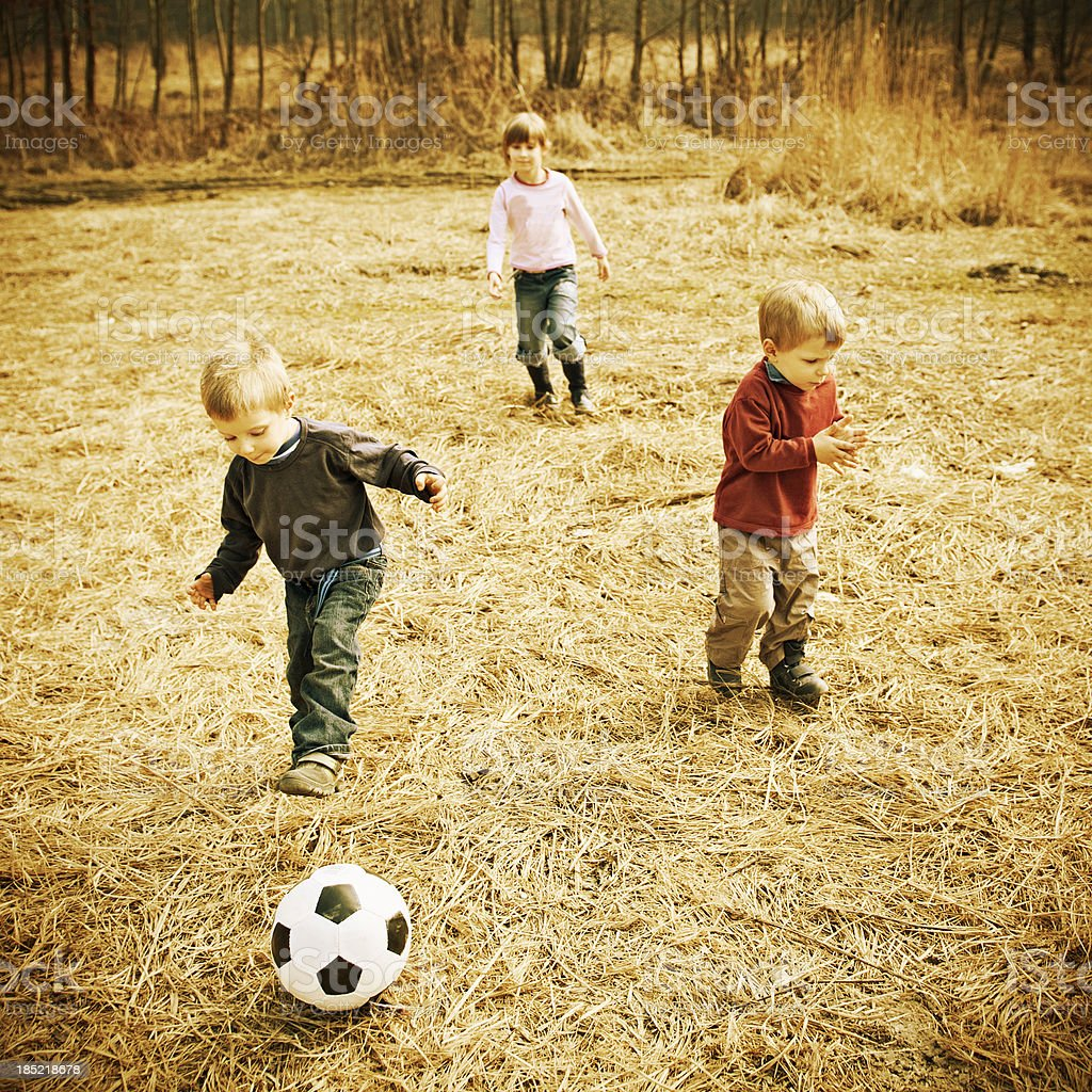 Children playing with football stock photo