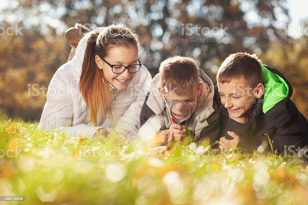 Children playing with magnifying glass in the park stock photo