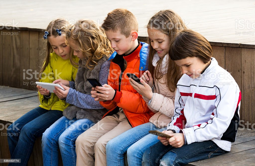 Children playing with mobile phones stock photo
