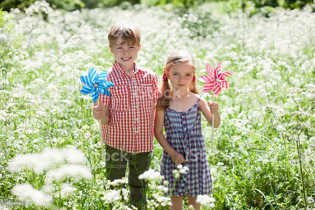 Children playing with pinwheels in field of flowers royalty-free stock photo