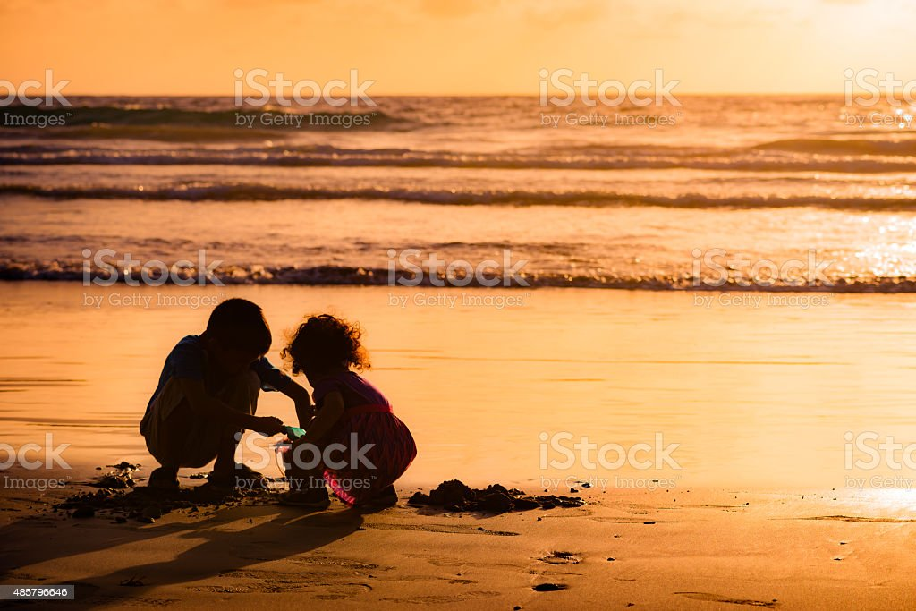 Children playing with sand by the sea at sunset Tobago stock photo
