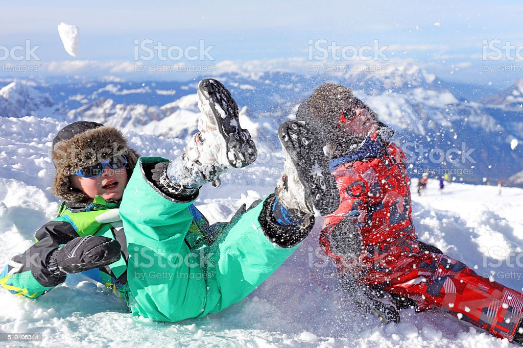 Children Playing with Snow in Swiss Mountains in Winter stock photo