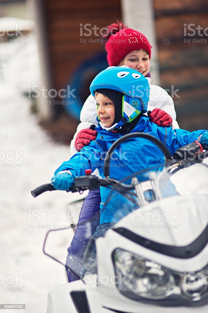 Children playing with snowmobile stock photo