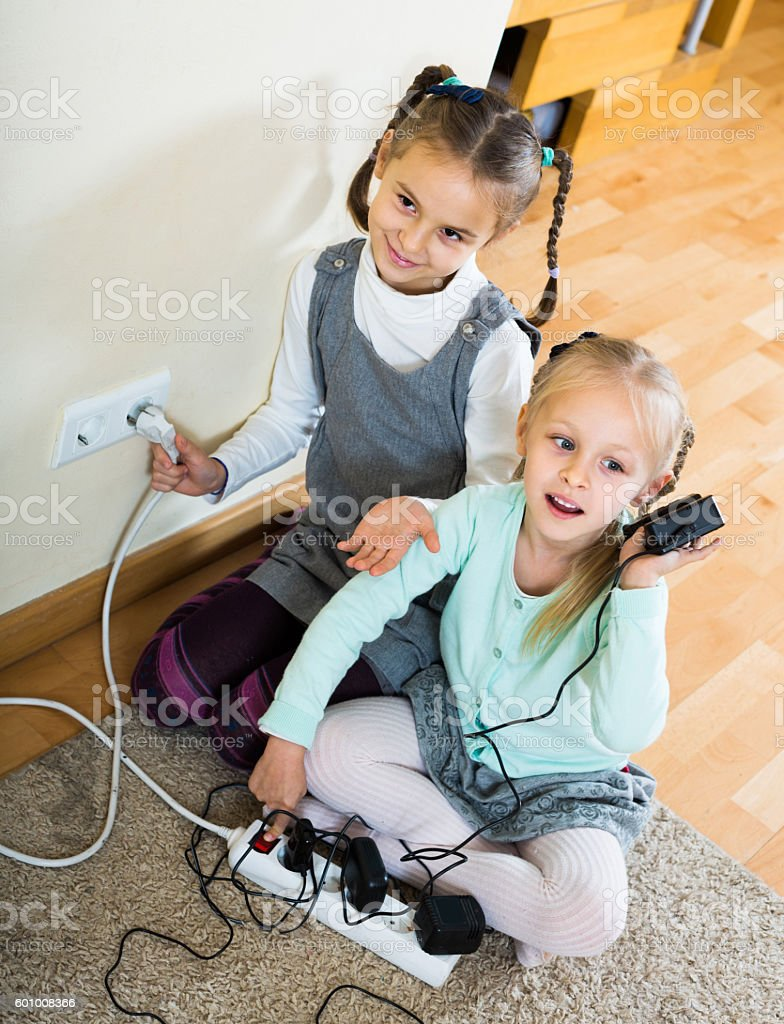children playing with sockets and electricity indoors stock photo