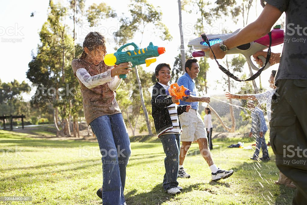 Children (9-12) playing with water guns stock photo
