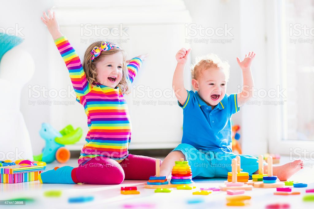 Children playing with wooden toys stock photo