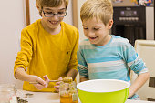 Children pouring honey into bowl, bakinng cookies