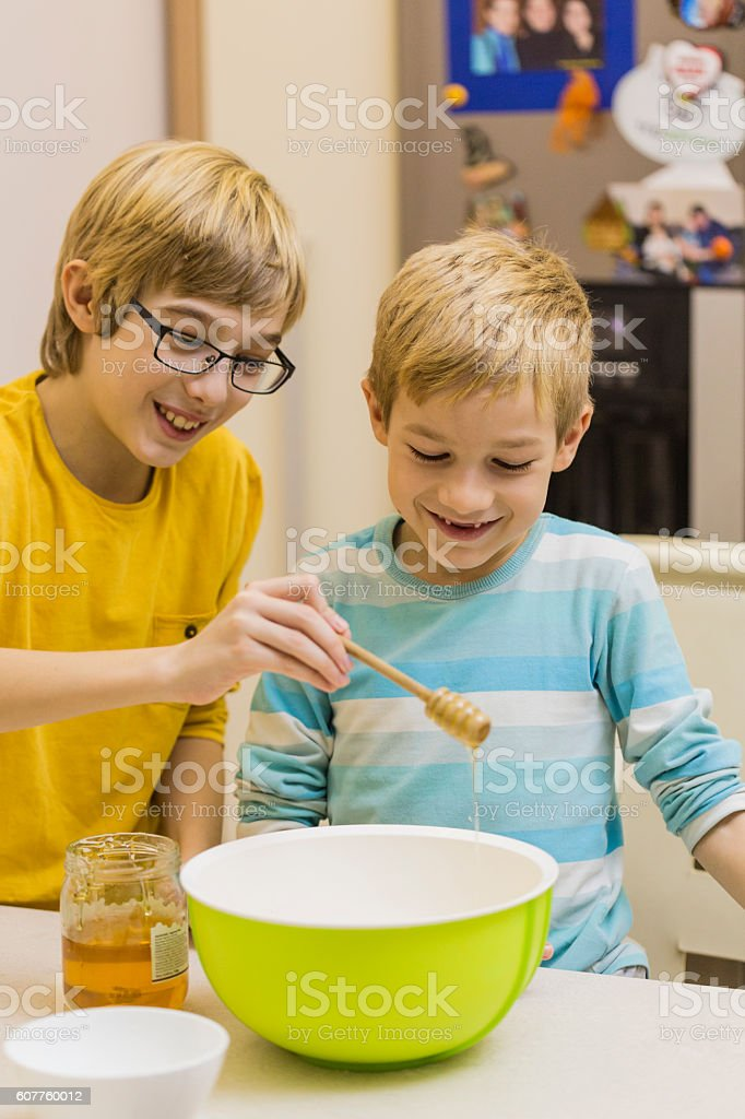 Children pouring honey into bowl, bakinng cookies stock photo