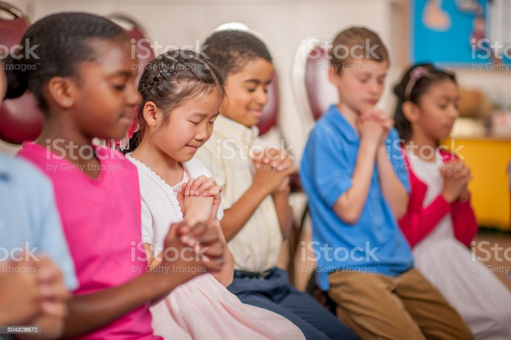 A multi-ethnic group of elementary age children are kneeling on the...