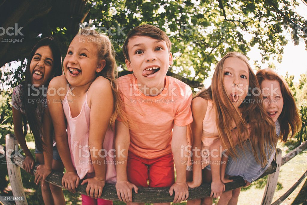 Children pulling silly faces at the camera in a park stock photo