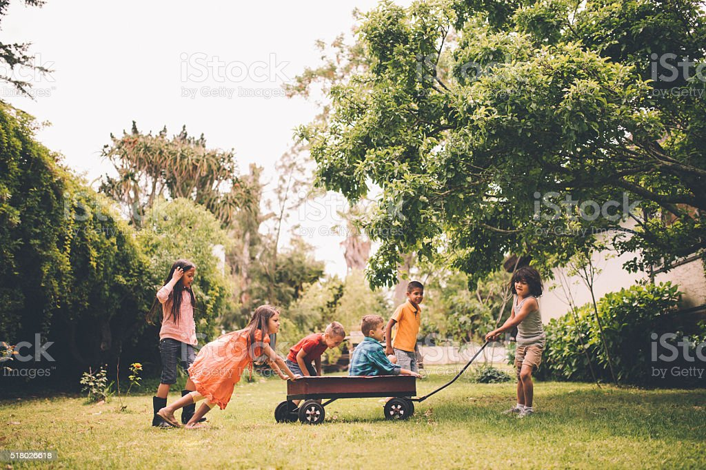 Children pushing and pulling friends in red wagon in park stock photo