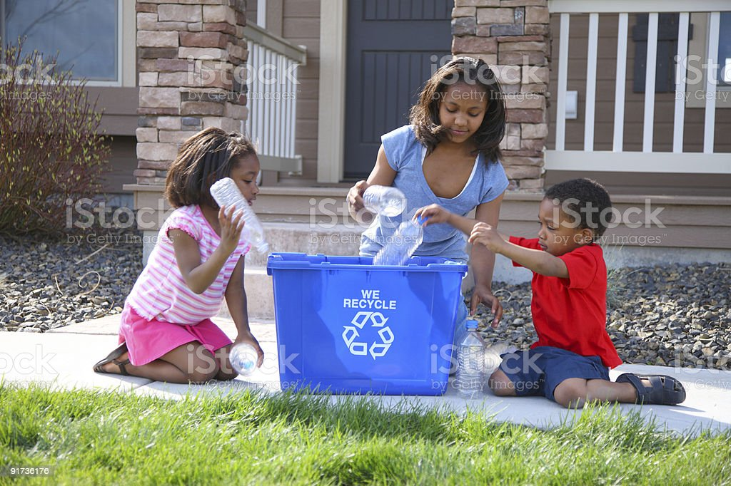 Children putting bottles in recycle bin stock photo