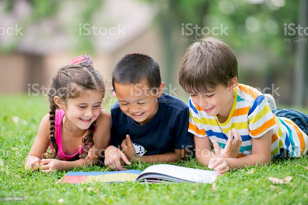 Children Reading a Book at the Park stock photo