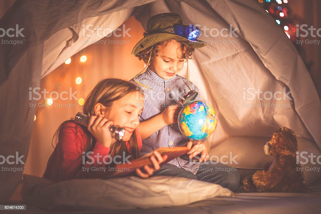 Children reading a book past their bedtime stock photo