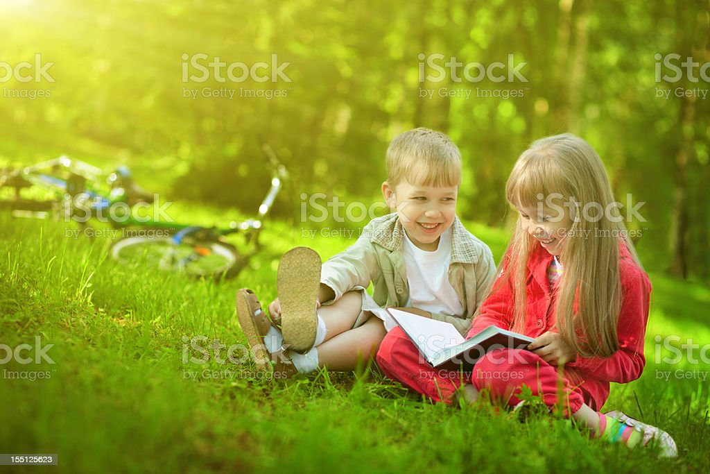 Children reading book in park royalty-free stock photo