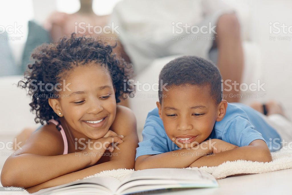 Children reading book with parents in the background royalty-free stock photo