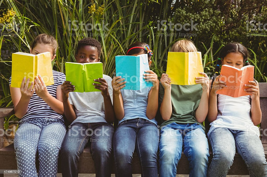 Children reading books at park stock photo