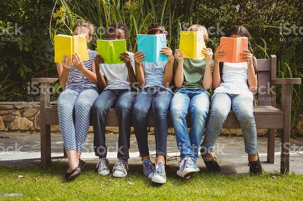 Children reading books at park stock photo