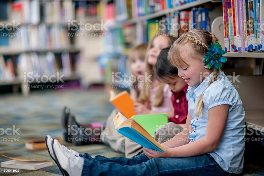 Children Reading Books in the Library stock photo