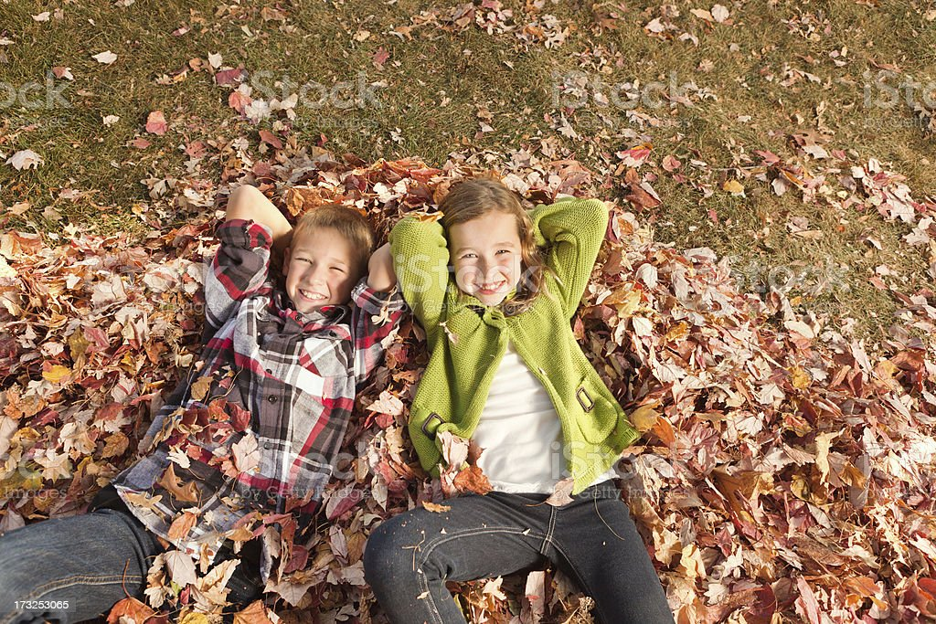Children Relaxing and Resting on Pile of Fall Leaves Hz royalty-free stock photo