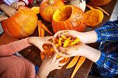 Children removing pulp from pumpkins to make Jack O'lanterns