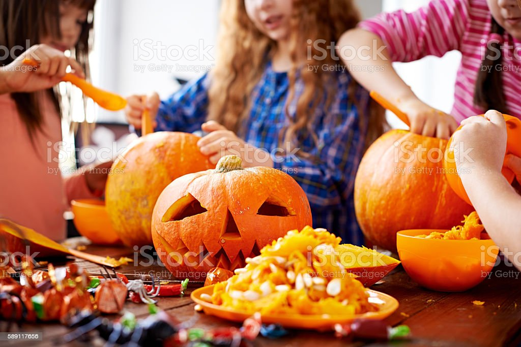 Children removing pumpkin seeds and pumpkin pulp to frighten people stock photo