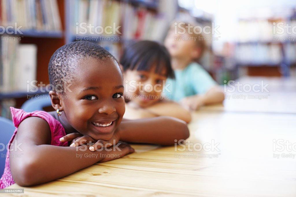 Children resting their heads on the library table stock photo