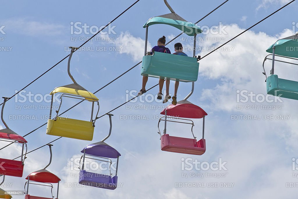 Children Ride a Tram Through Blue Sky Above royalty-free stock photo