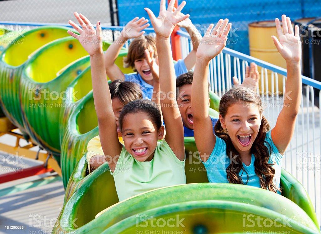 Children riding a green roller coaster stock photo