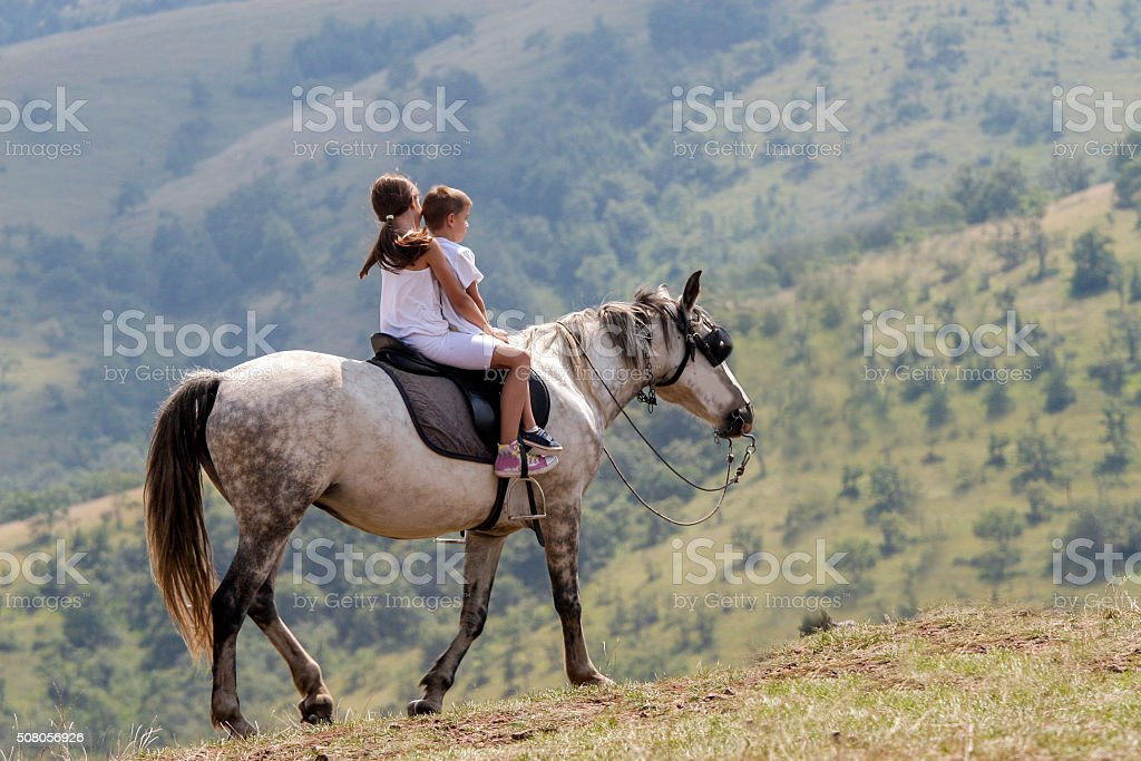 Children riding a horse in mountain and enjoying stock photo