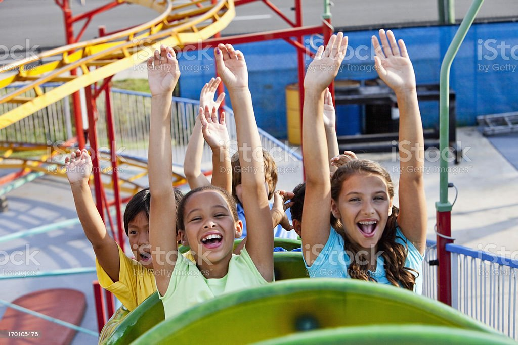 Children riding a roller coaster stock photo
