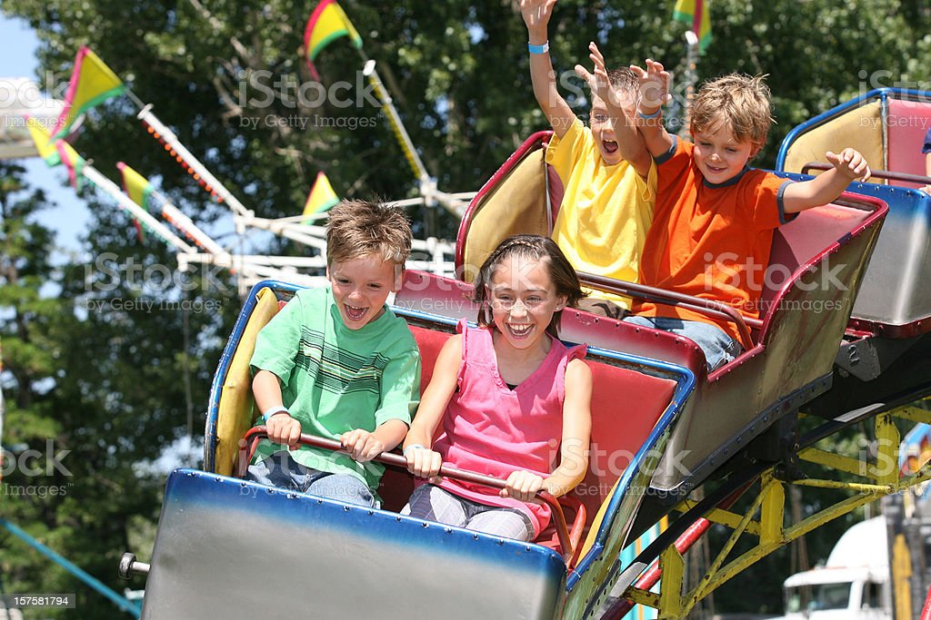 Children riding on a roller coaster stock photo