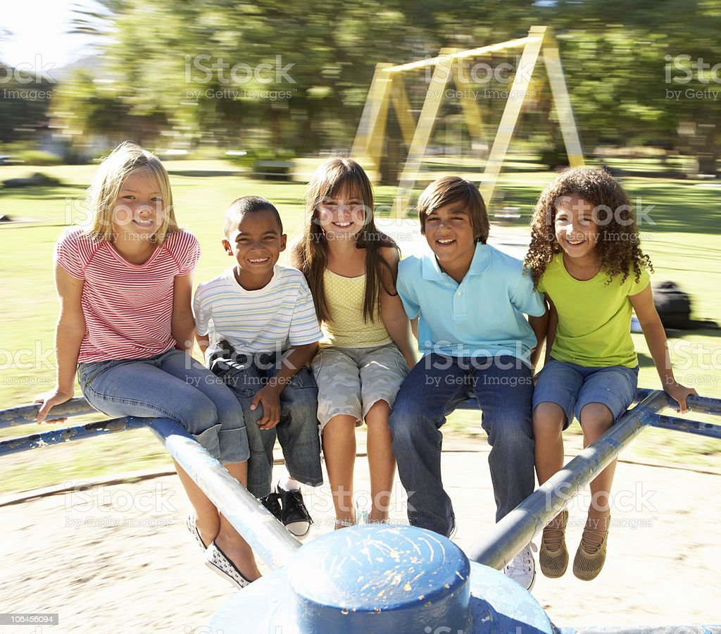 Children Riding On Roundabout In Playground royalty-free stock photo