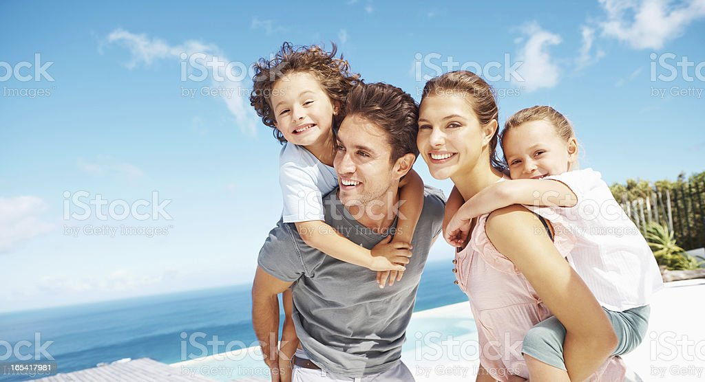 Children riding piggyback with parents at a beach royalty-free stock photo
