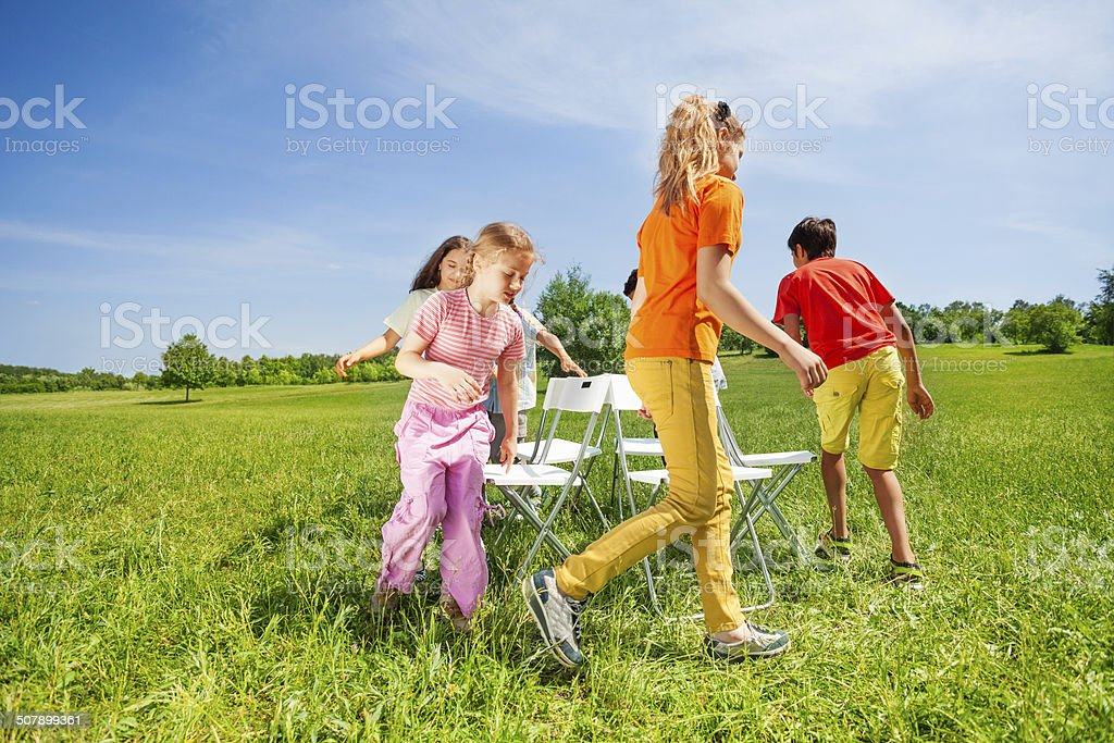 Children run around chairs playing a game outside stock photo