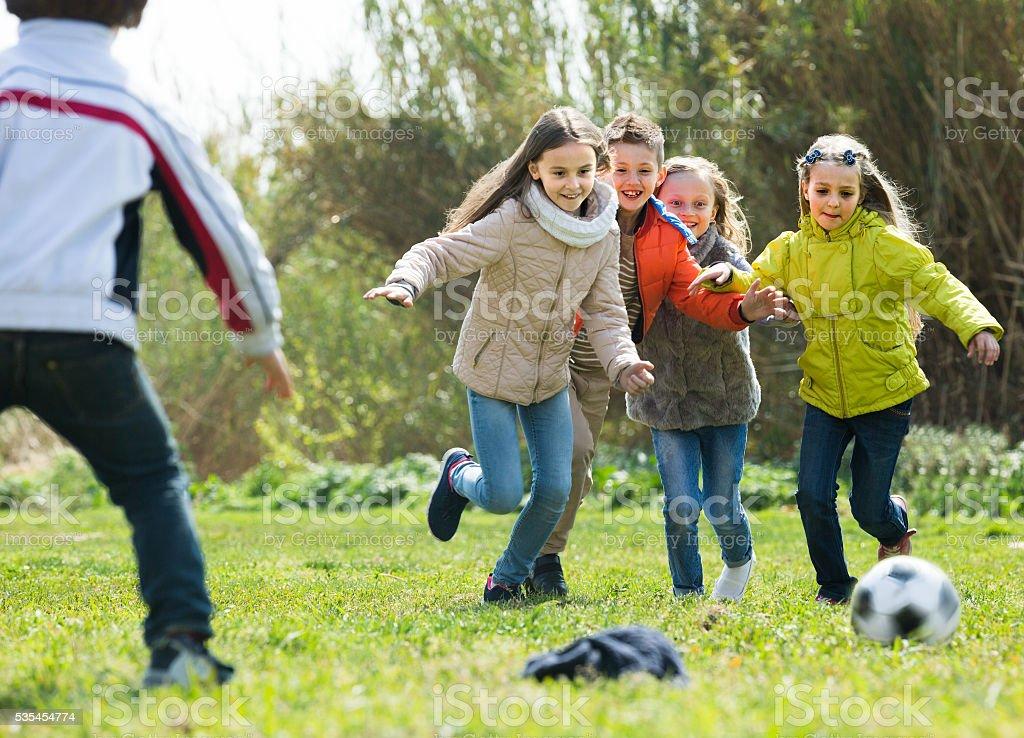 children running after ball stock photo