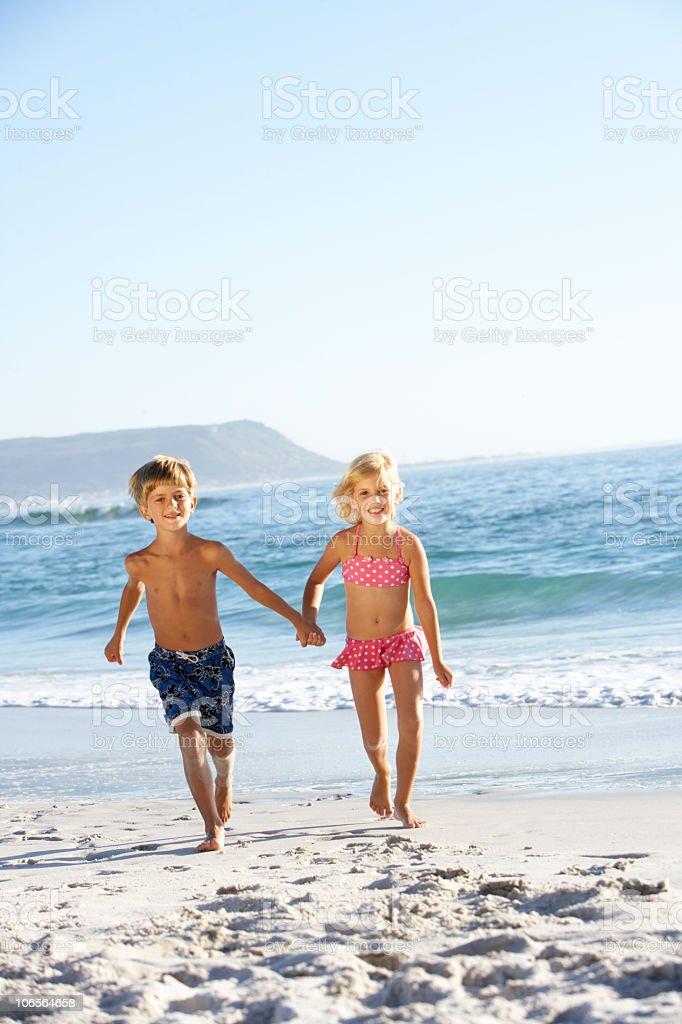 Children running along sandy beach stock photo