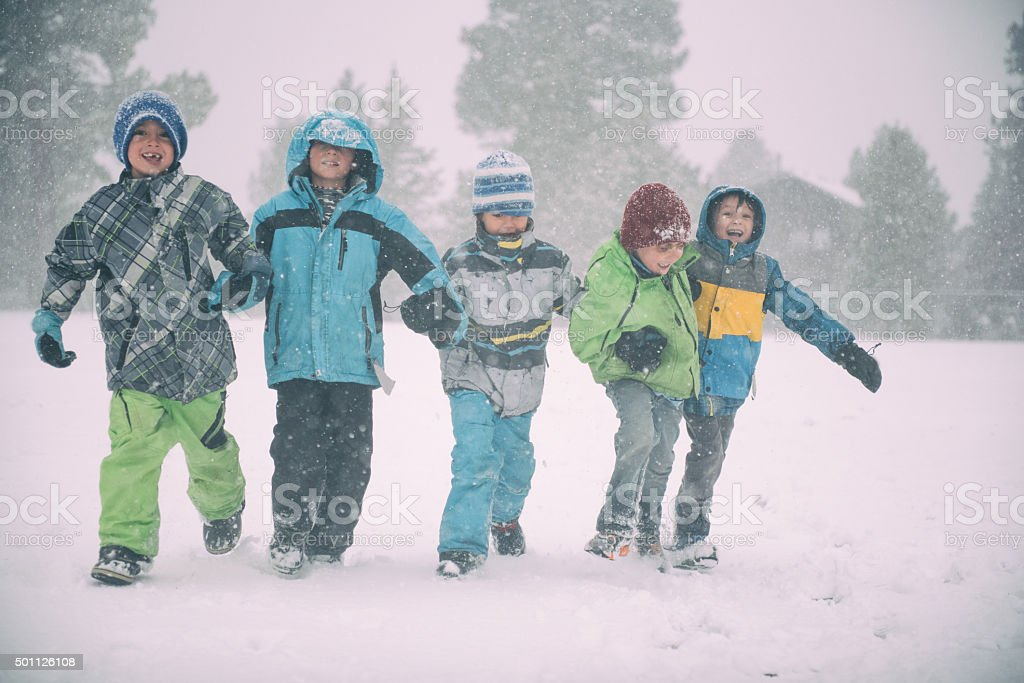 Children running and playing in the snow during a storm stock photo