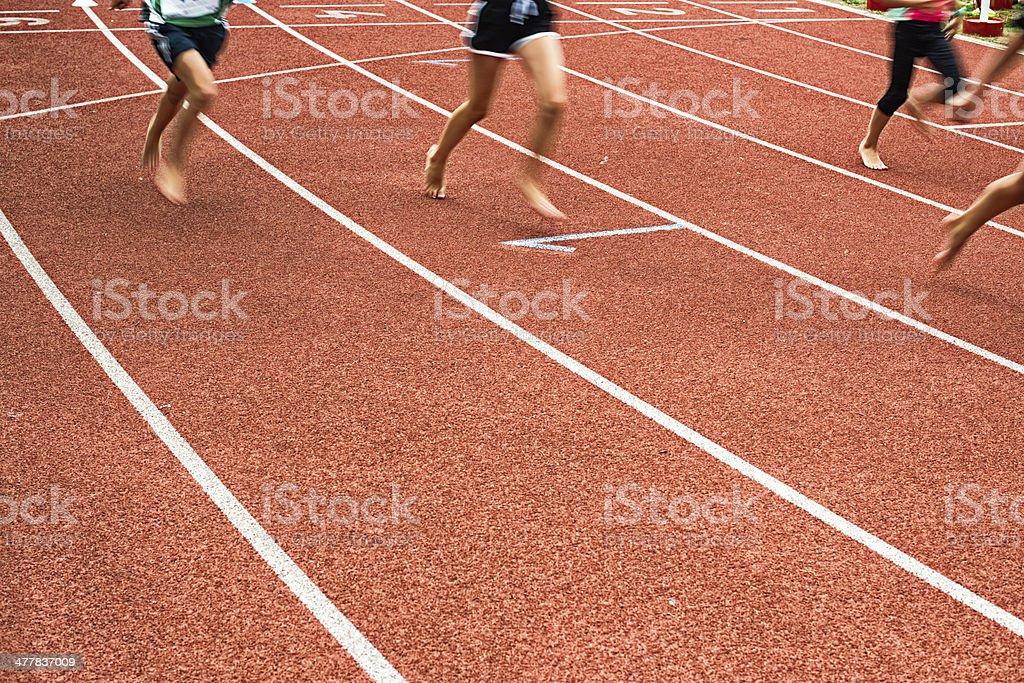 children running barefoot on tartan track stock photo