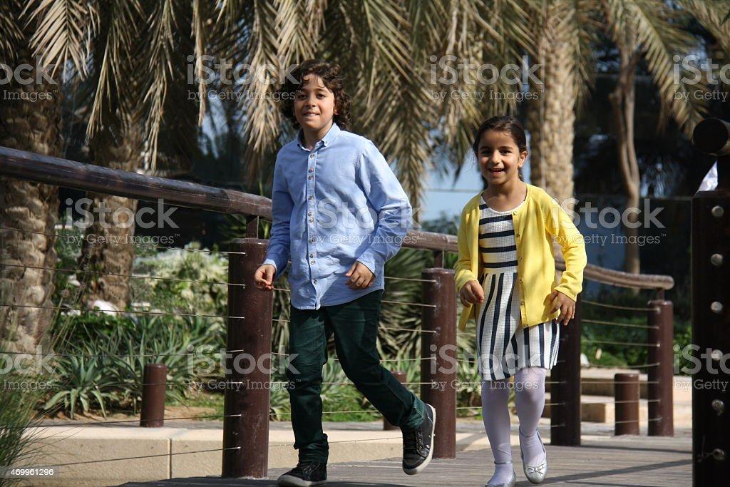 Children running in the park, Dubai, UAE stock photo