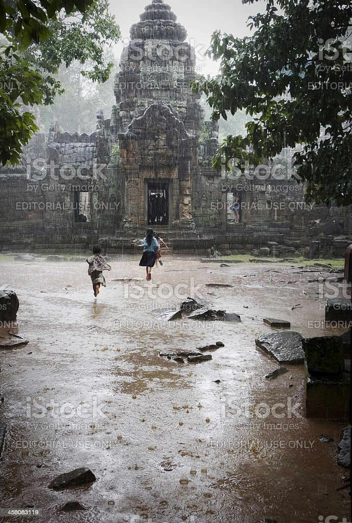 children running in the rain at angkor royalty-free stock photo