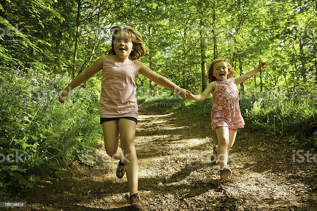 Children running laughing down forest trail stock photo