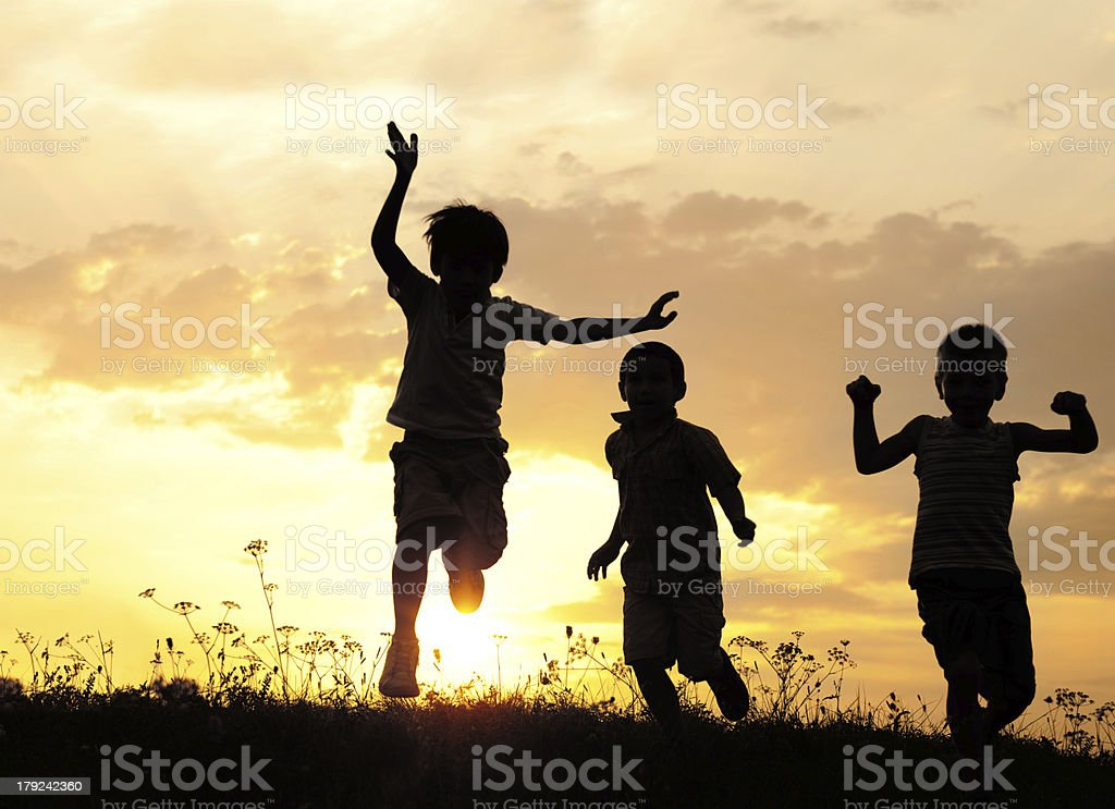 Children running on meadow at sunset stock photo