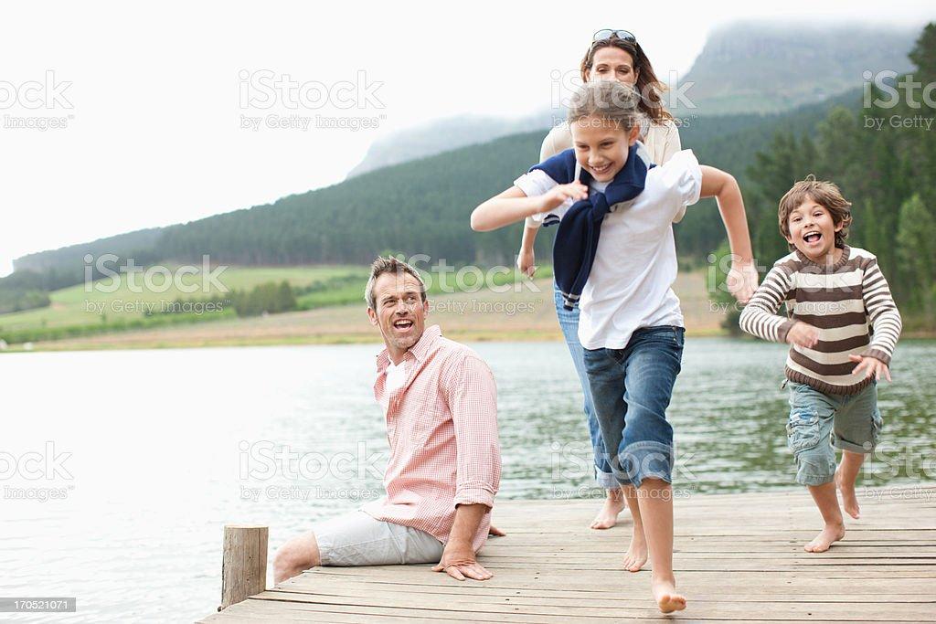 Children running on pier by lake stock photo
