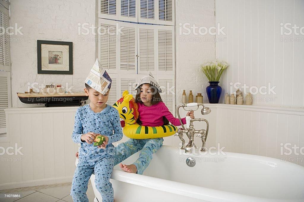 Children sat on bath tub royalty-free stock photo