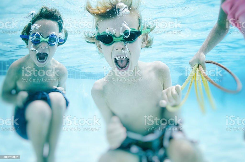 Children screaming underwater playfully stock photo